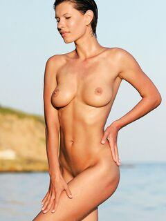 Голенькая загорелая девушка позирует на пляже