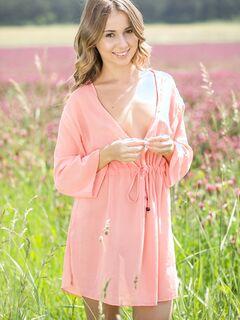 Девушка снимает платье и позирует голая в поле