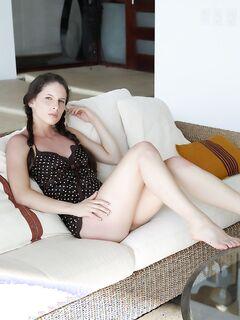 Шатенка с косичками оголяет грудь и письку на диване