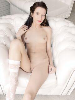 Обнаженная красотка с бритой киской сидит в кресле