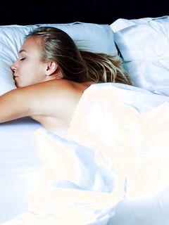 Голенькая девушка в очках показала попку в постели