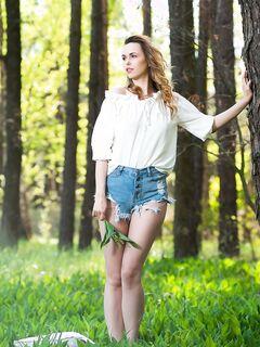 Девушка снимает шорты и показывает киску в лесу