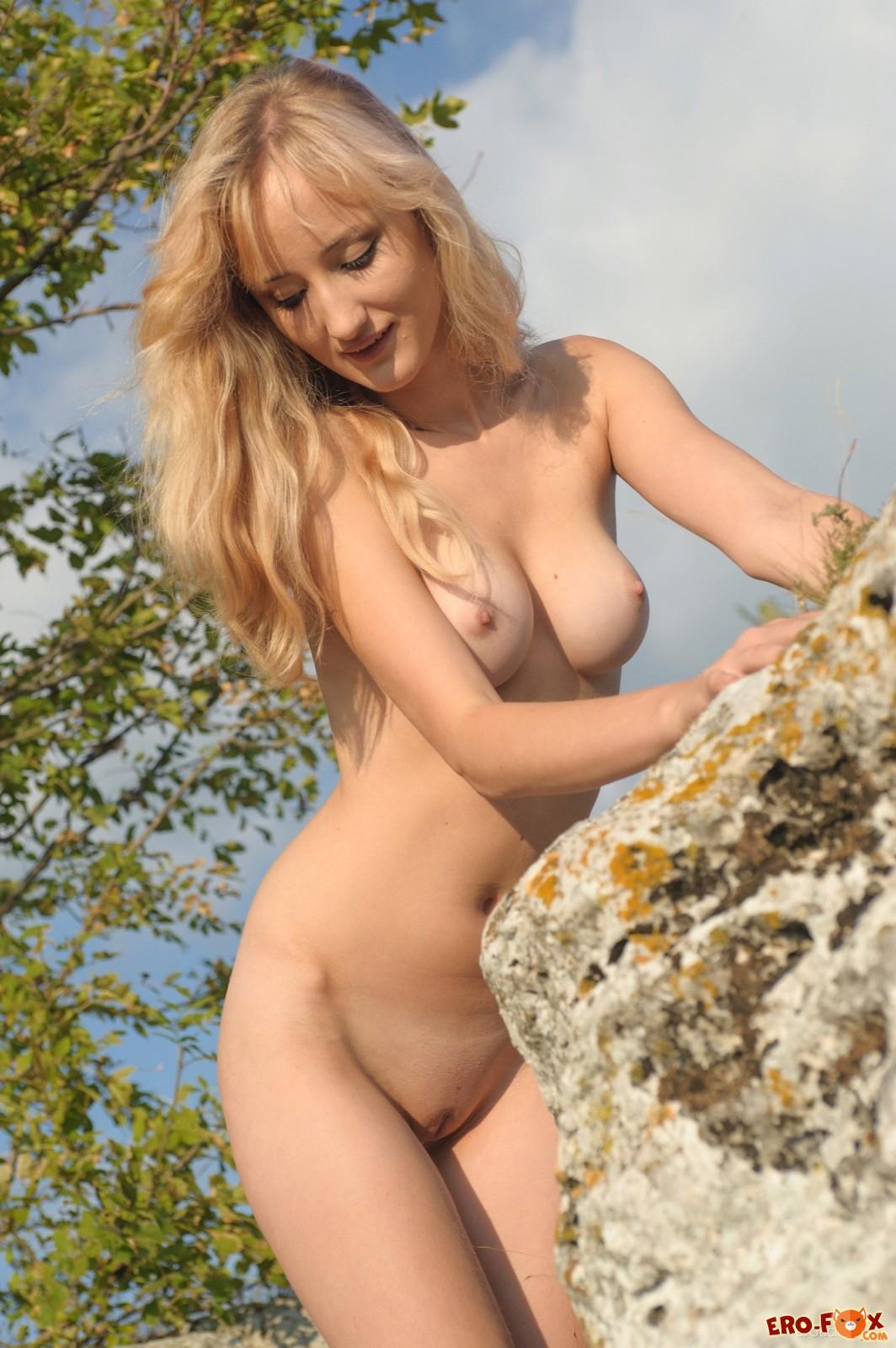 Худая девица позирует голой среди скал на природе