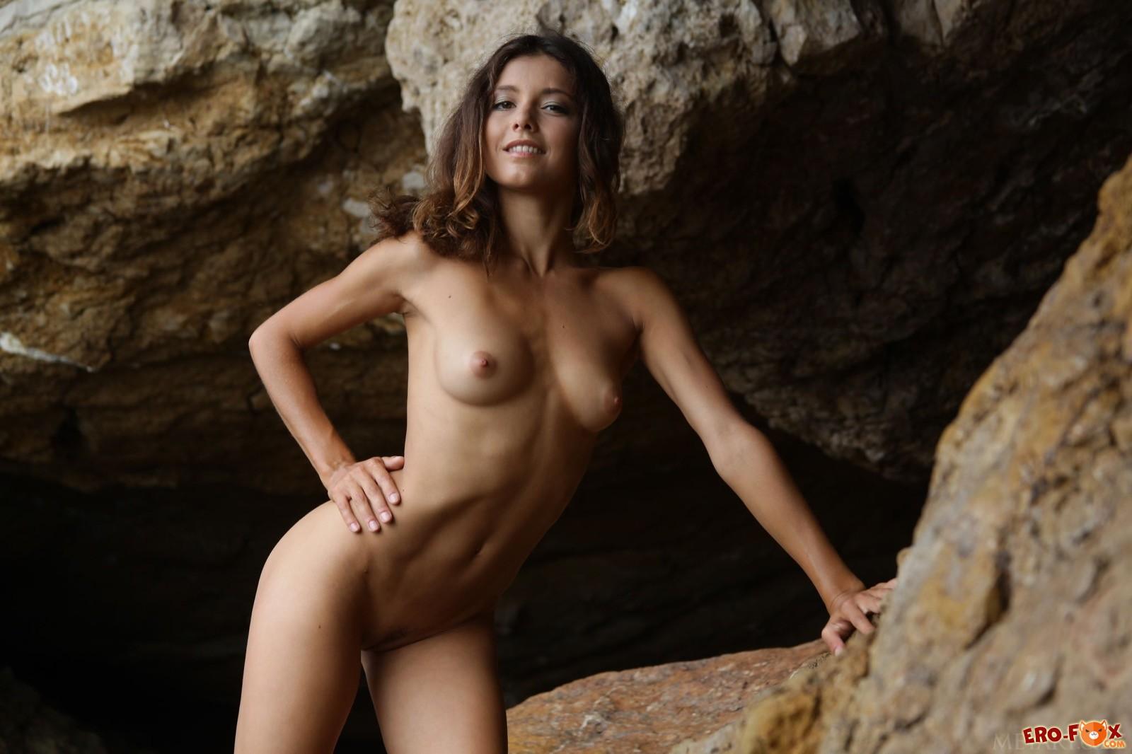 Голенькая худышка грациозно выгибается у скалы