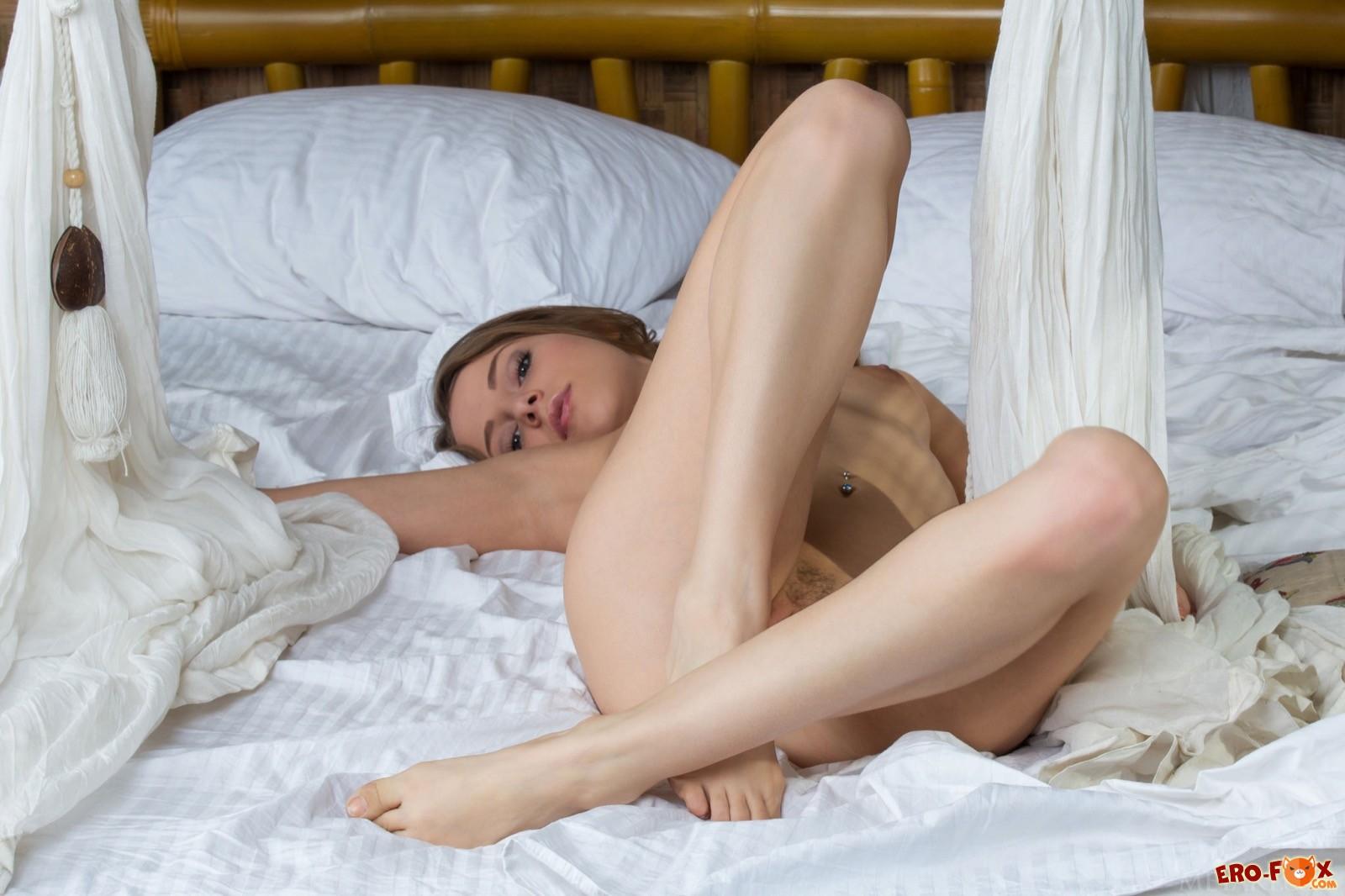 Молодая голая девушка с маленькой грудью в постели