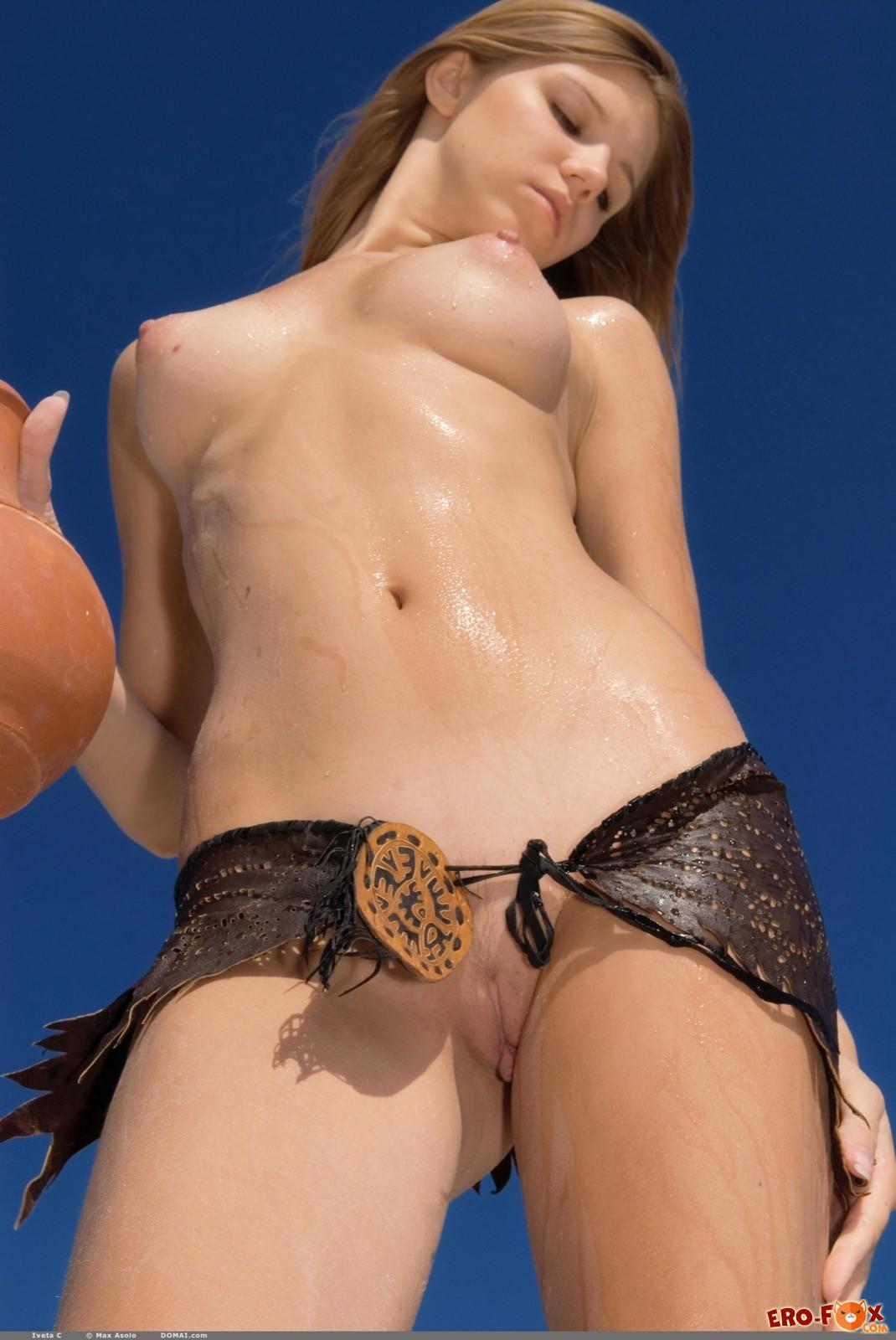 Обнаженная девушка обливается водой из кувшина