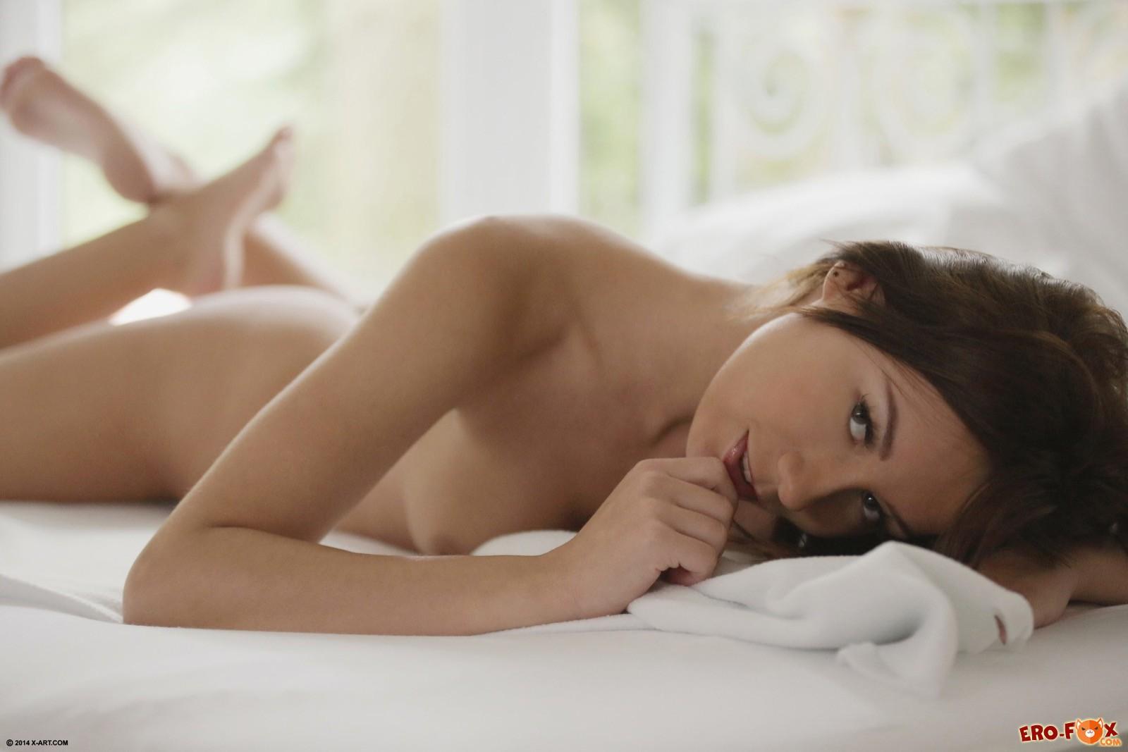 Симпатичная шатенка с голыми сиськами в постели
