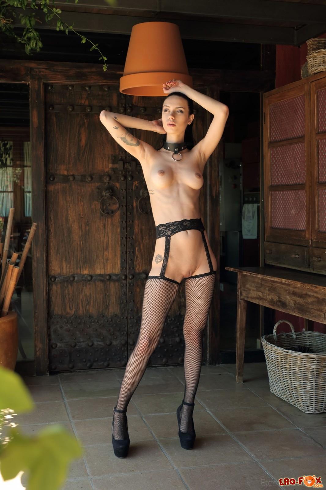 Девушка в чулках и ошейнике эротично позирует