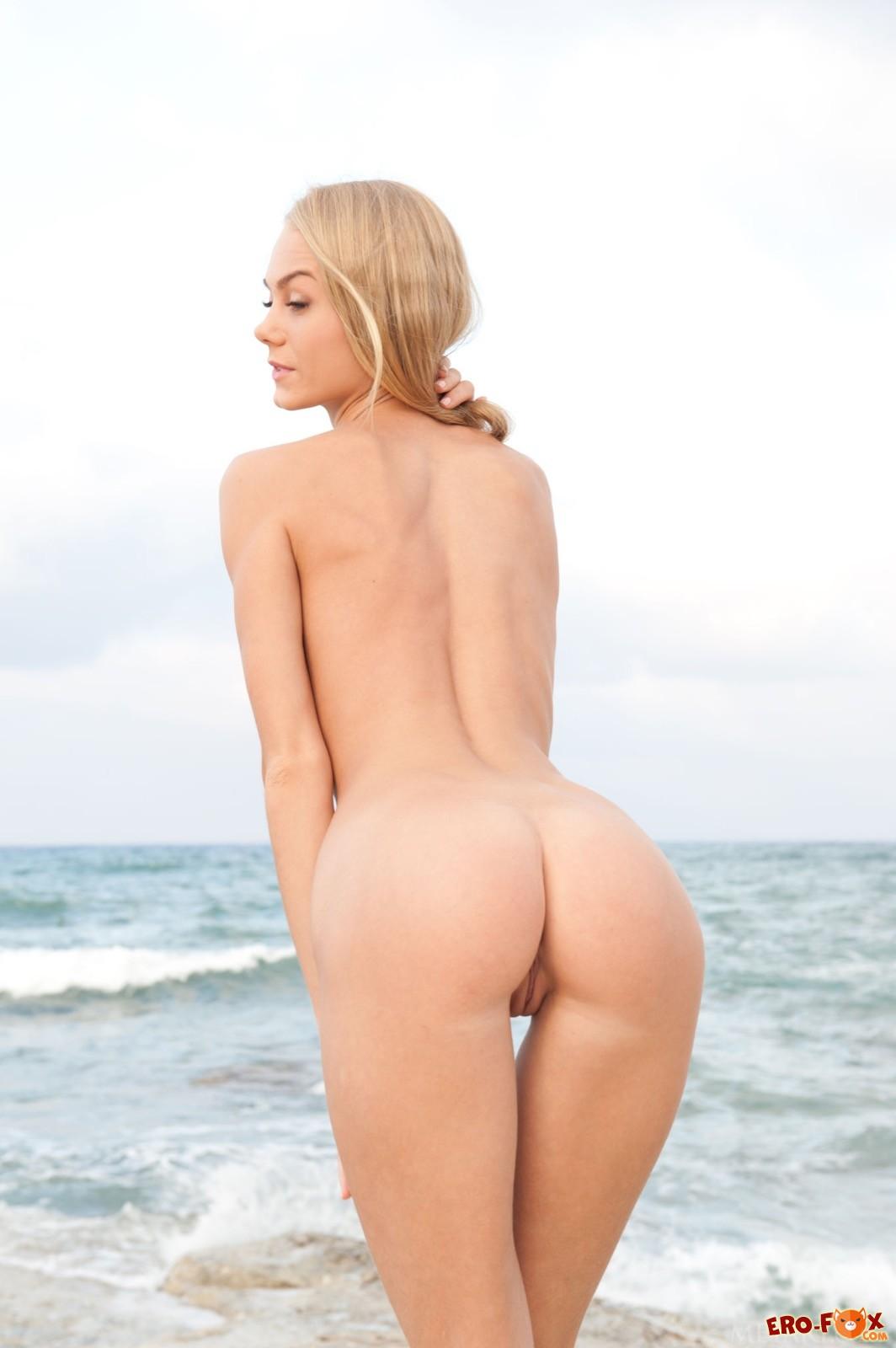 Худая блондинка сняла платье и позирует на пляже