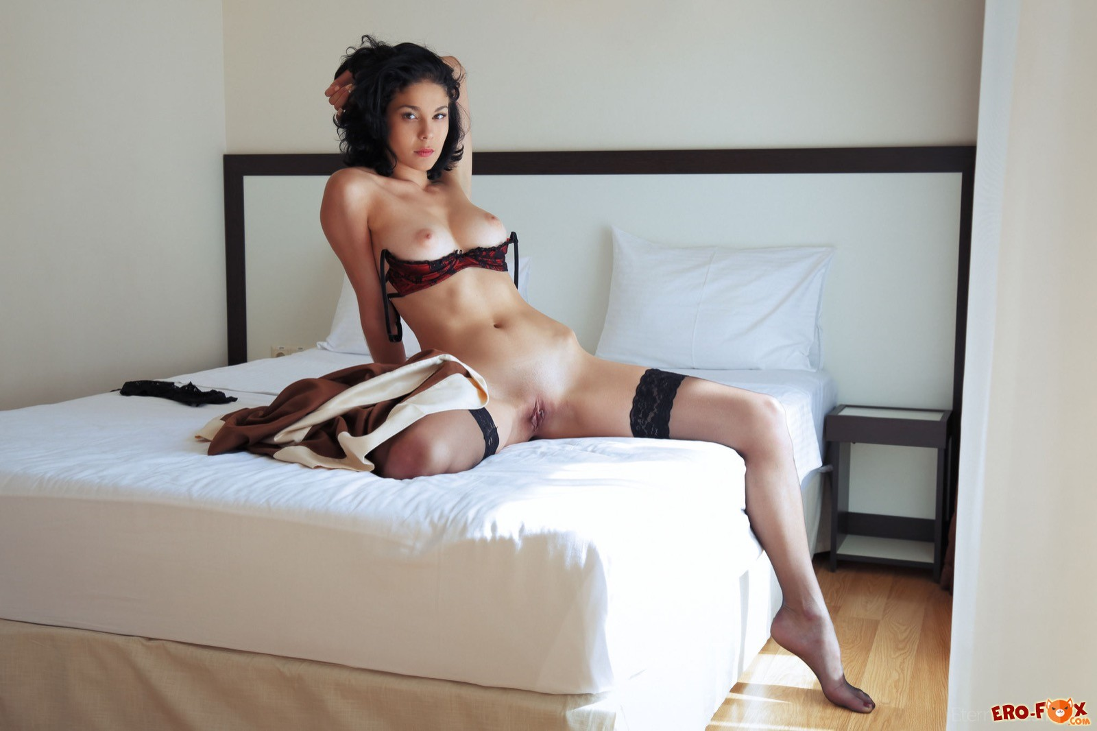 Красотка в чулках оголяет торчащие сиськи в постели
