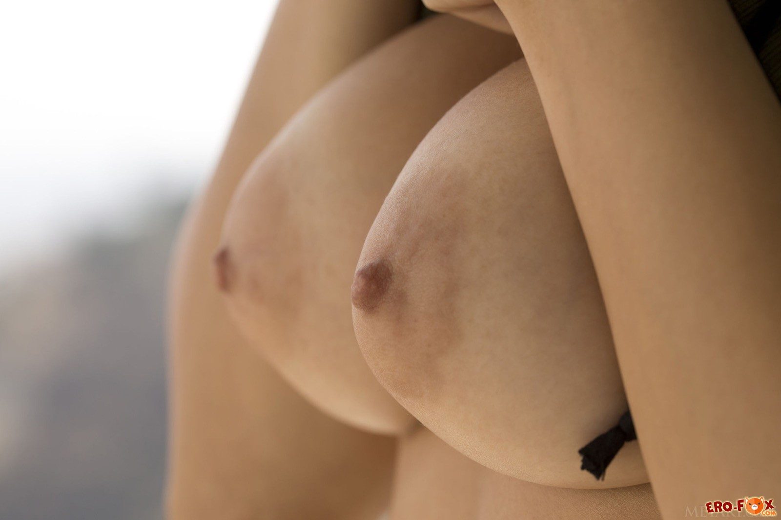 Сексуальная милашка без лифчика позирует в кафе
