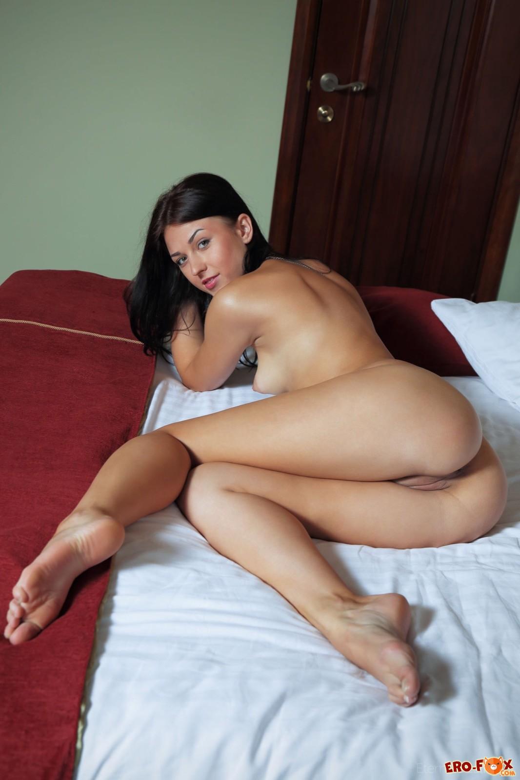 Брюнетка в сексуальных колготках позирует в спальне