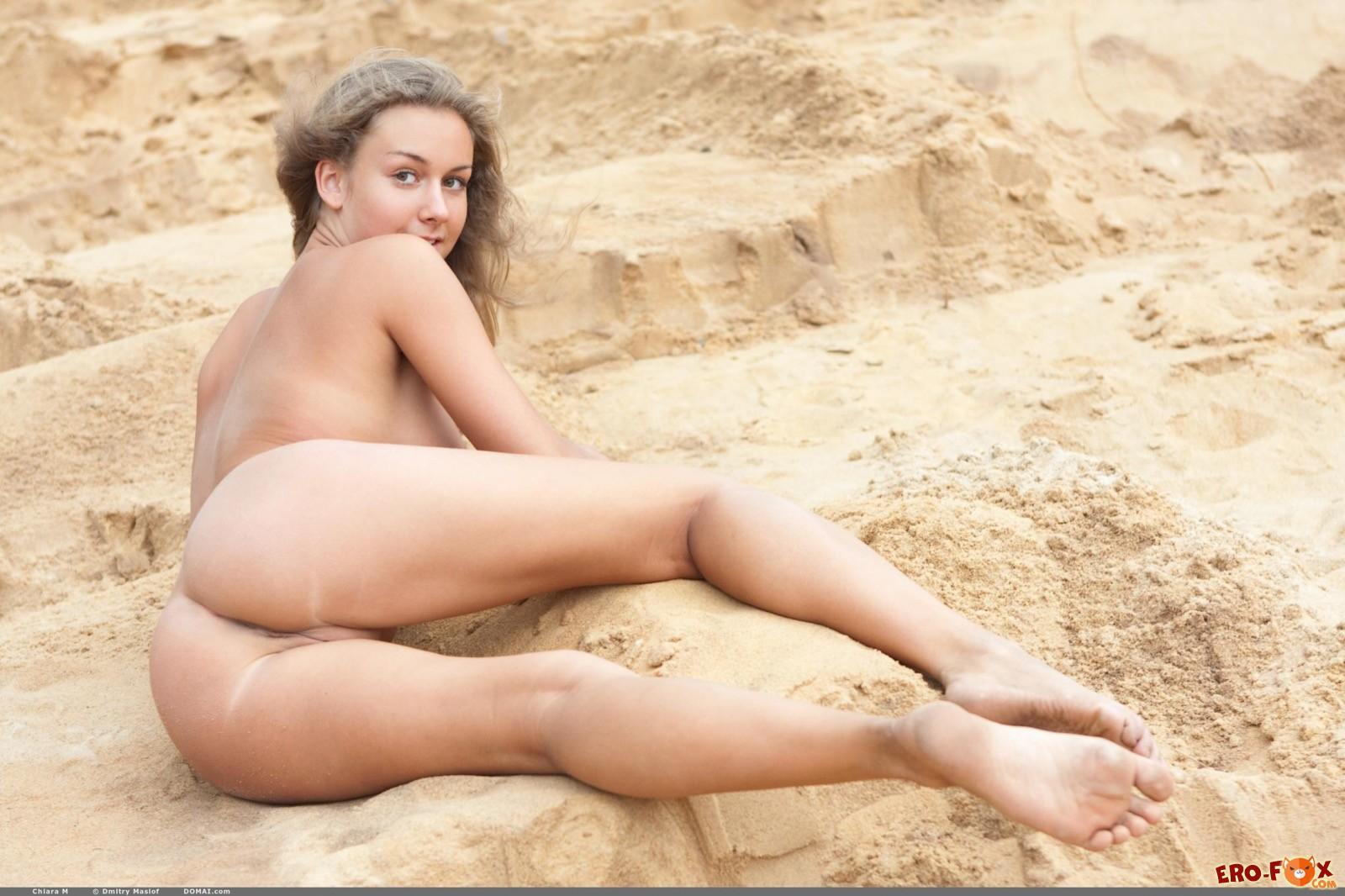 Раздетая модель с загорелым телом валяется в песке