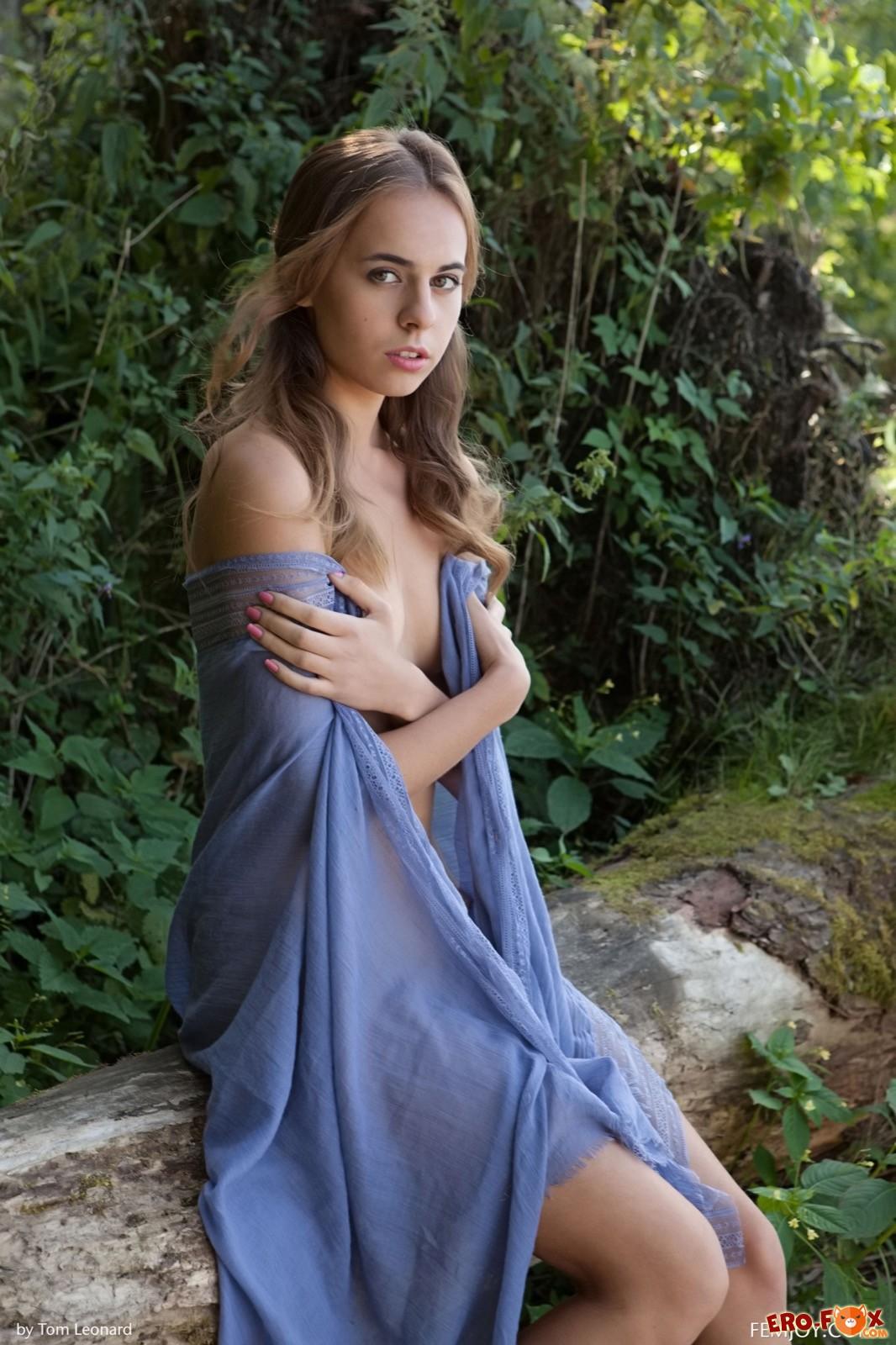 Голая девушка с платком эротично позирует на природе