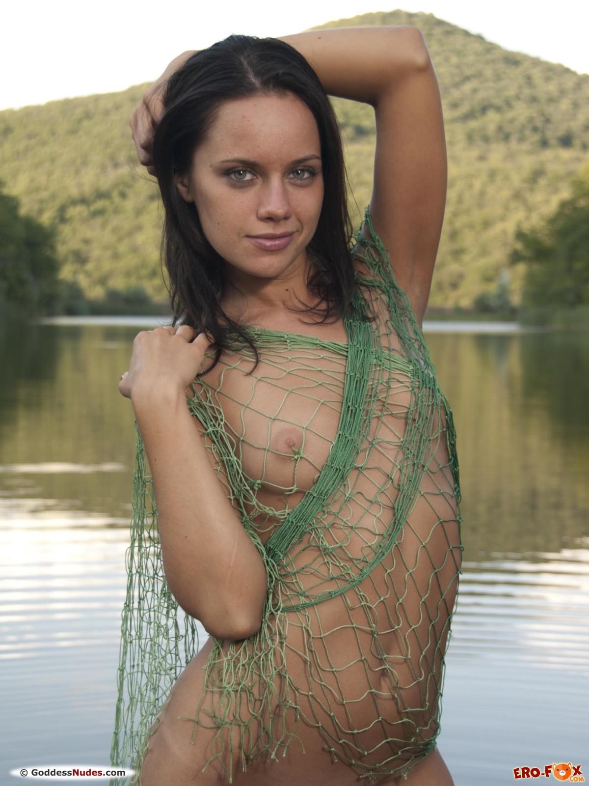 Голая девушка загорает и купается на озере