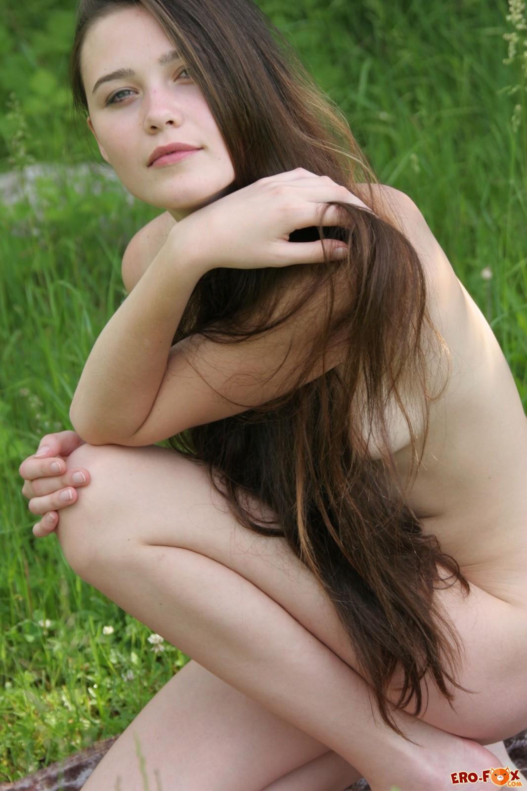 Длинноволосая голая девушка позирует на природе