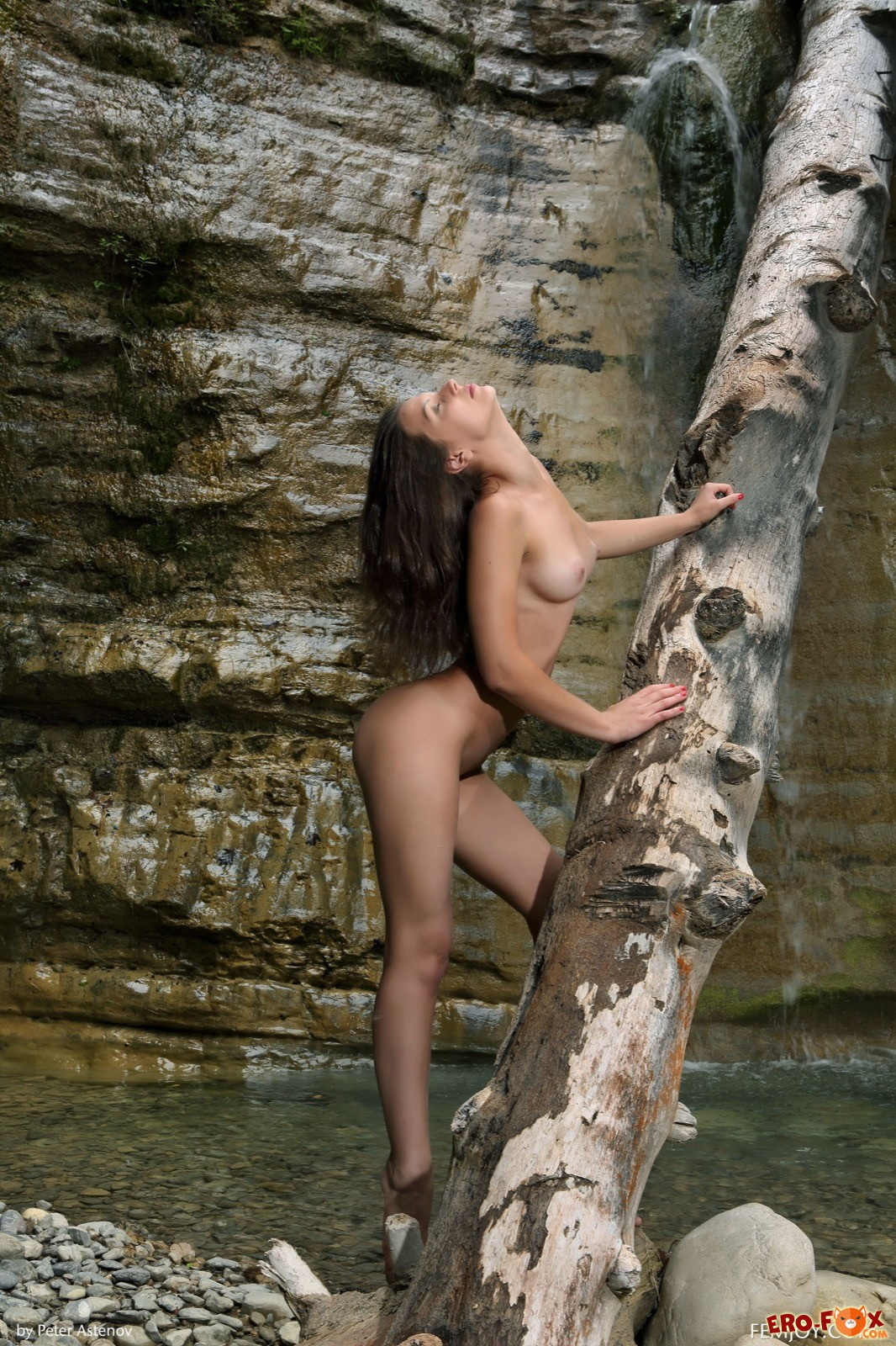 Голая девушка с накаченной попкой у водопада