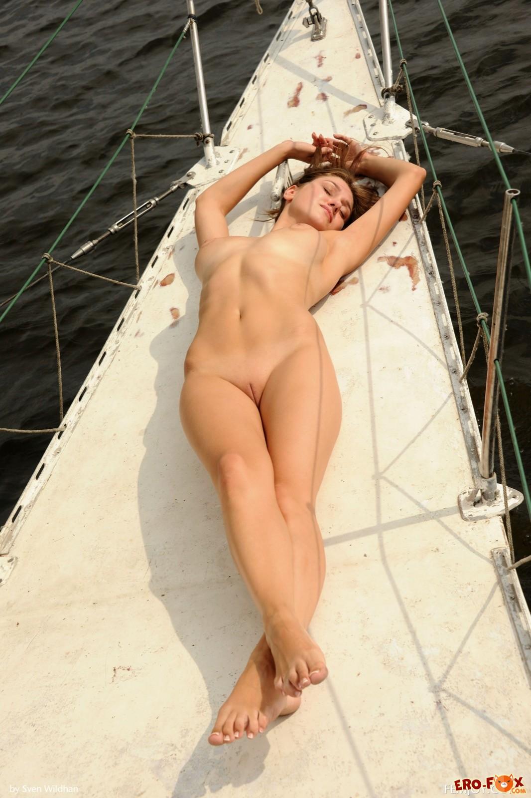 Красивая девушка оголилась и позирует на яхте