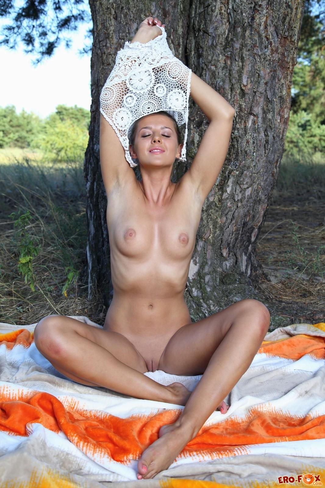 Красивая девушка снимает трусики и позирует в лесу