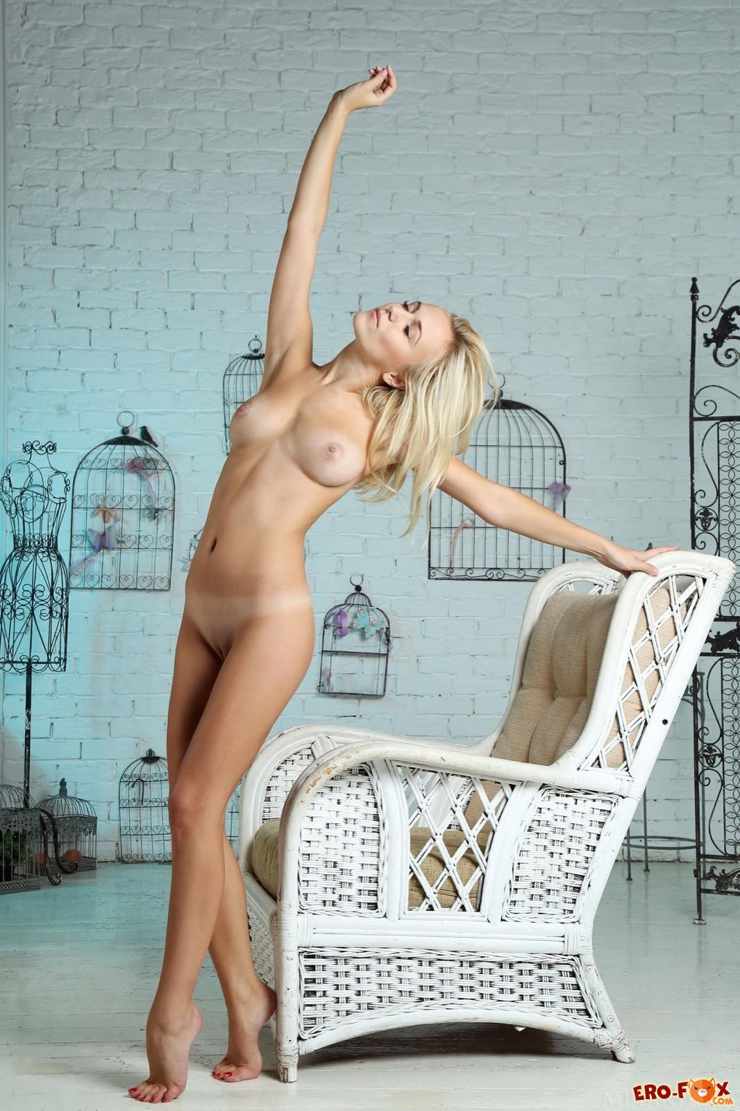 Голая блондинка с красивым телом позирует у кресла