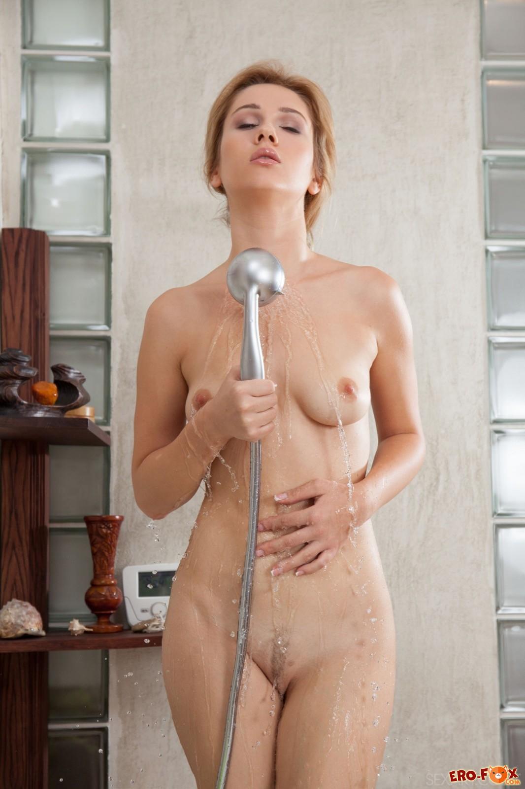 Голая девушка эротично обливается водой в ванной