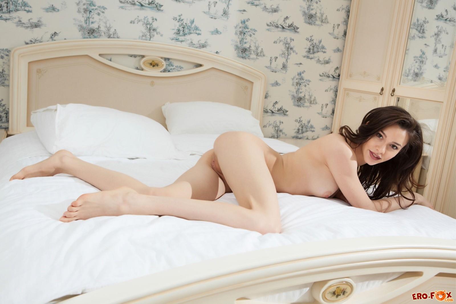 Обнаженная девушка позирует на кровати .