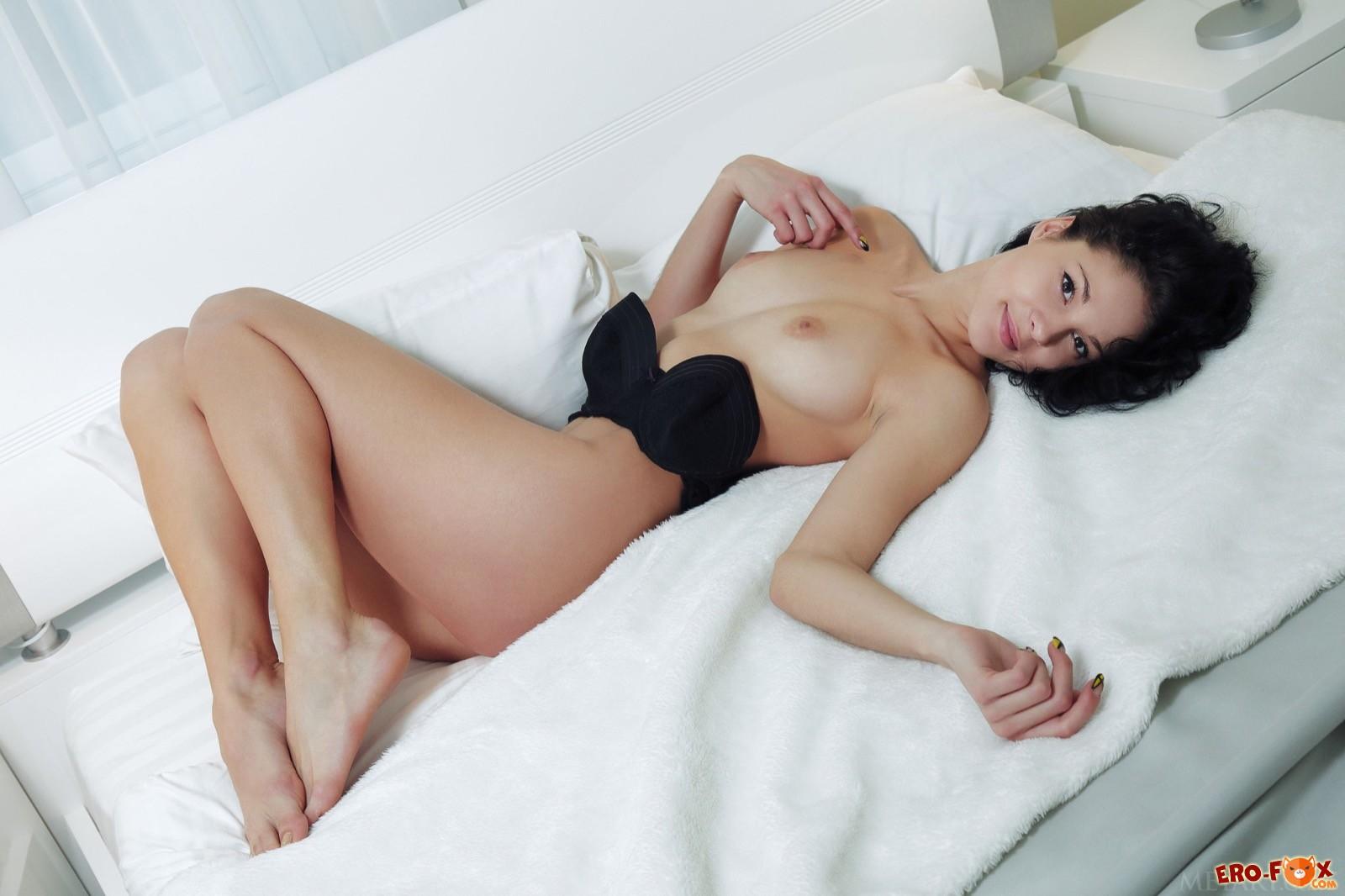 Голая брюнетка на кровати .
