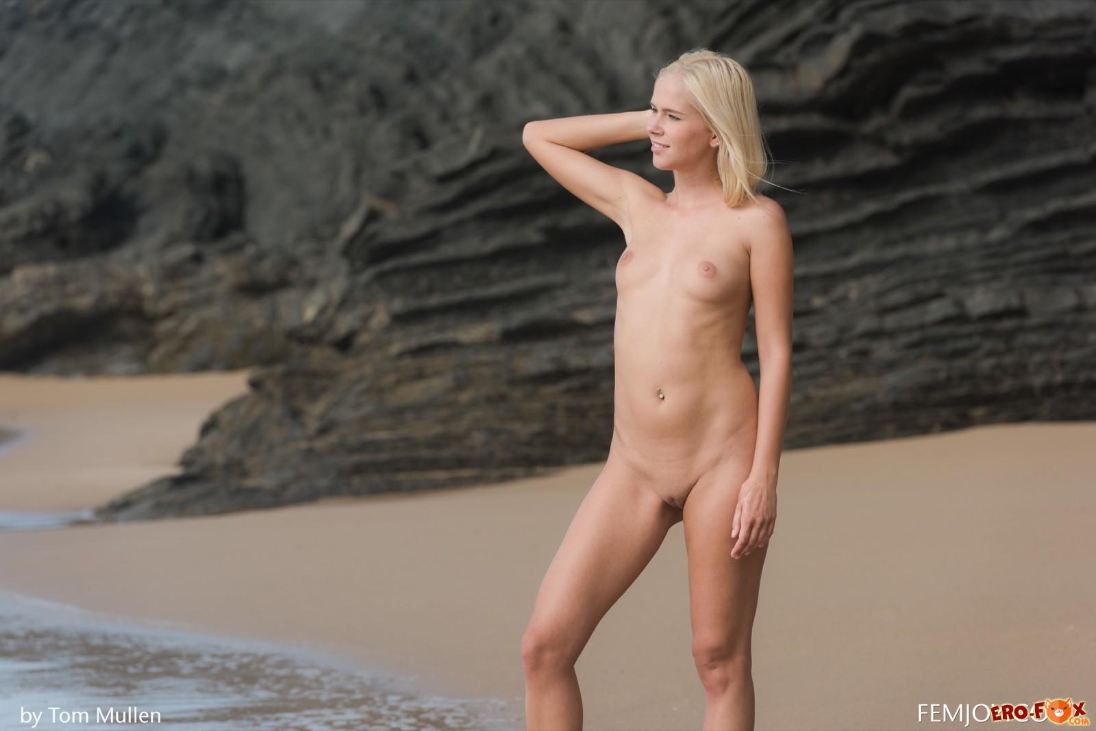 Сексуальная блондинка без одежды гуляет по пляжу