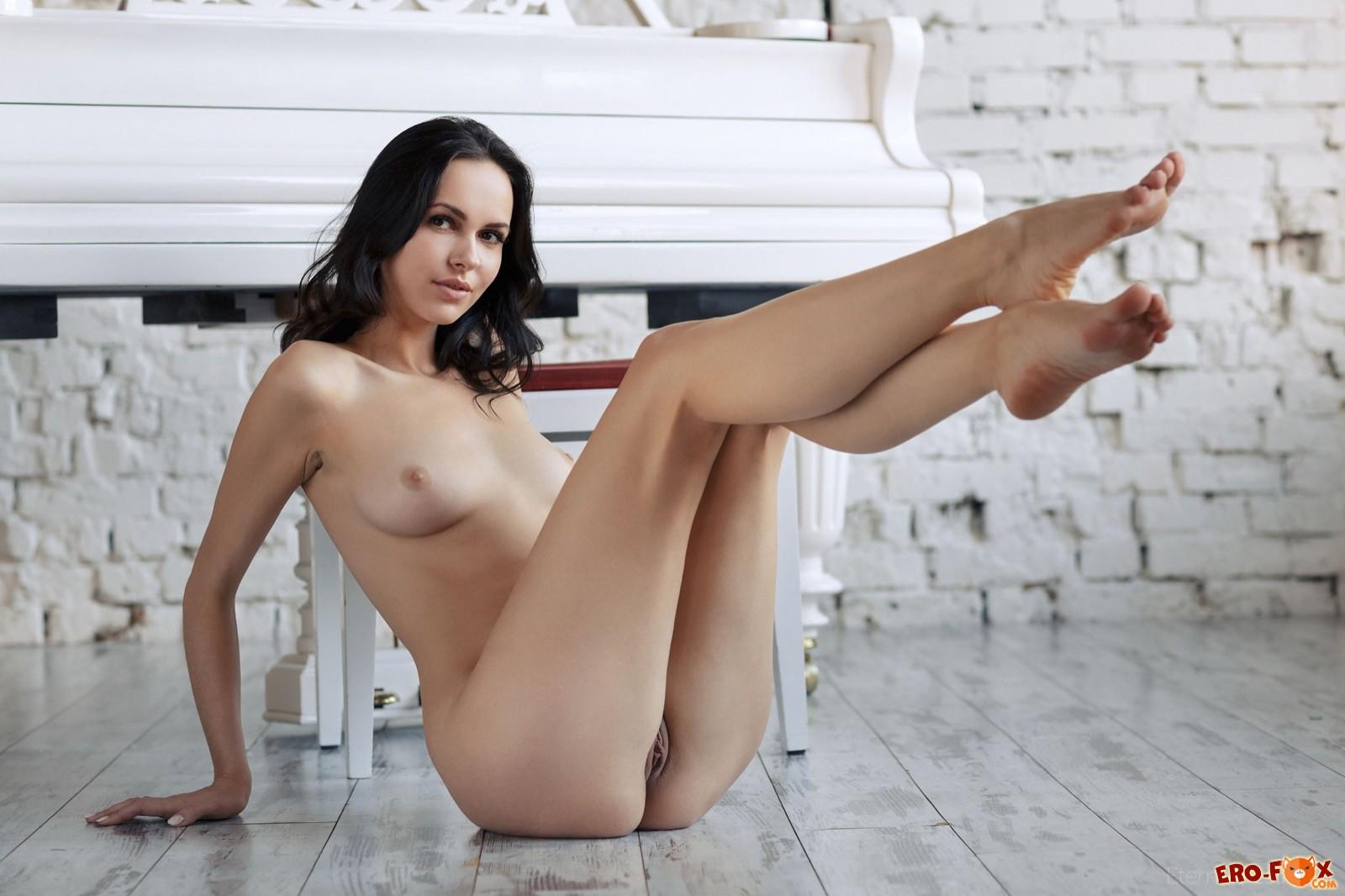 Красивая голая брюнетка у рояля