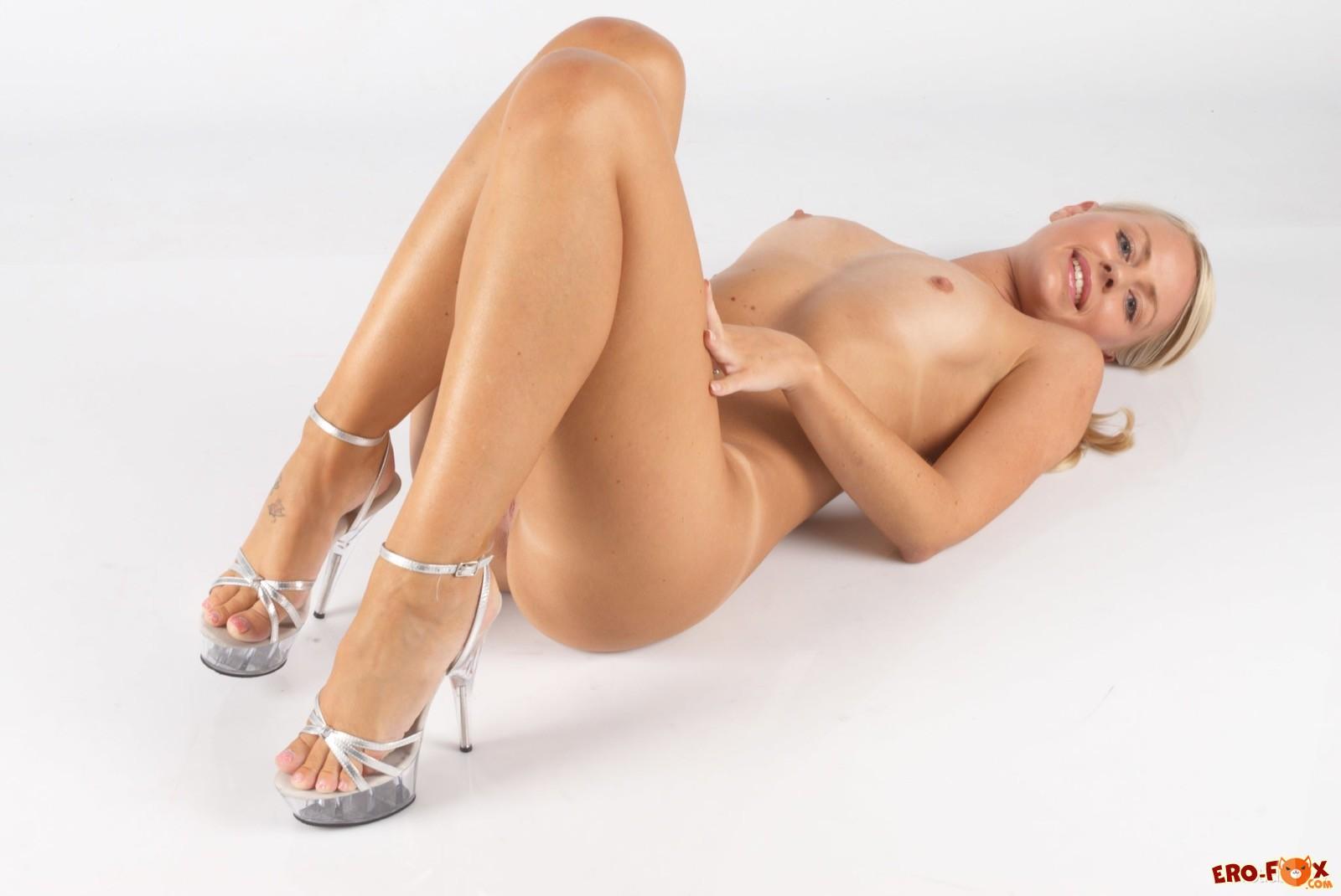 Красивая светловолосая девушка позирует на каблуках