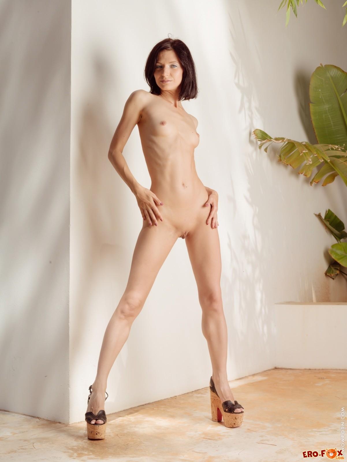 Худая голая девушка на каблуках