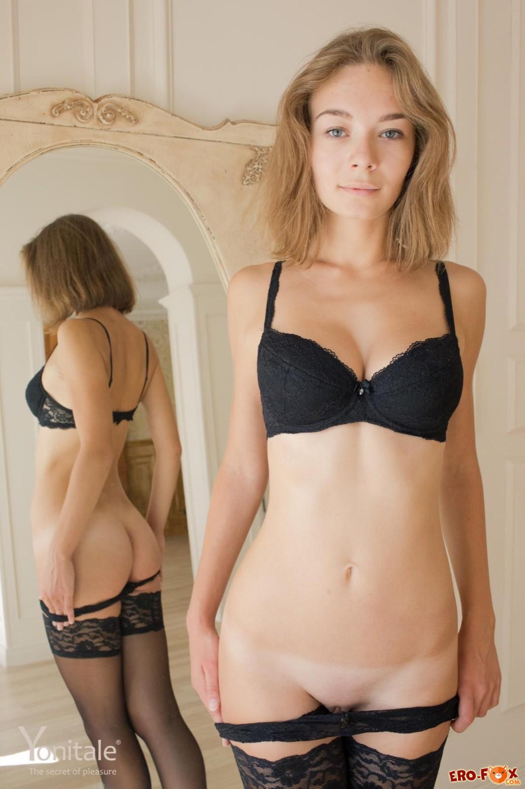 Голая девица в чулках перед зеркалом