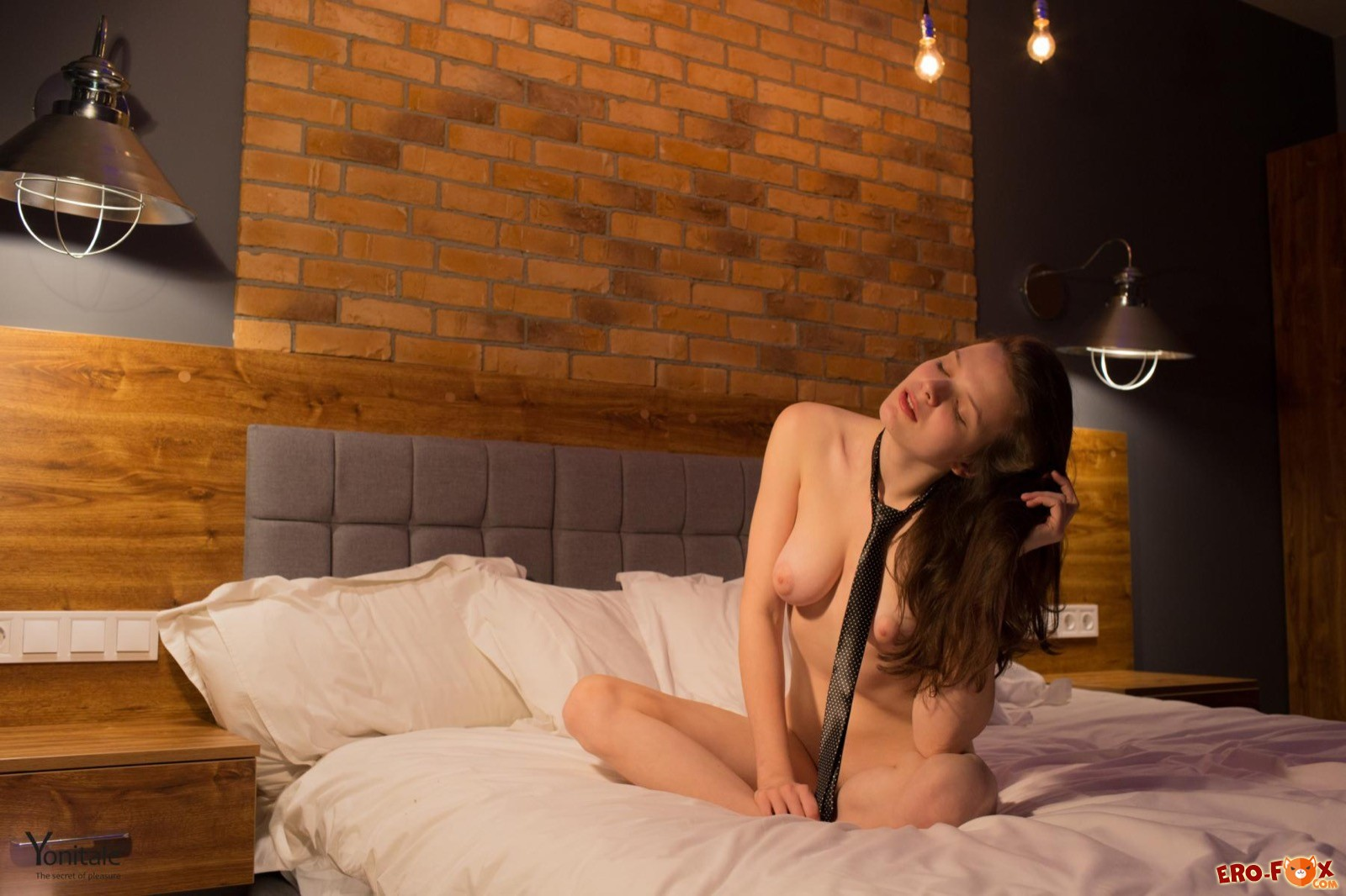 Голенькая девка в галстуке позирует в постели