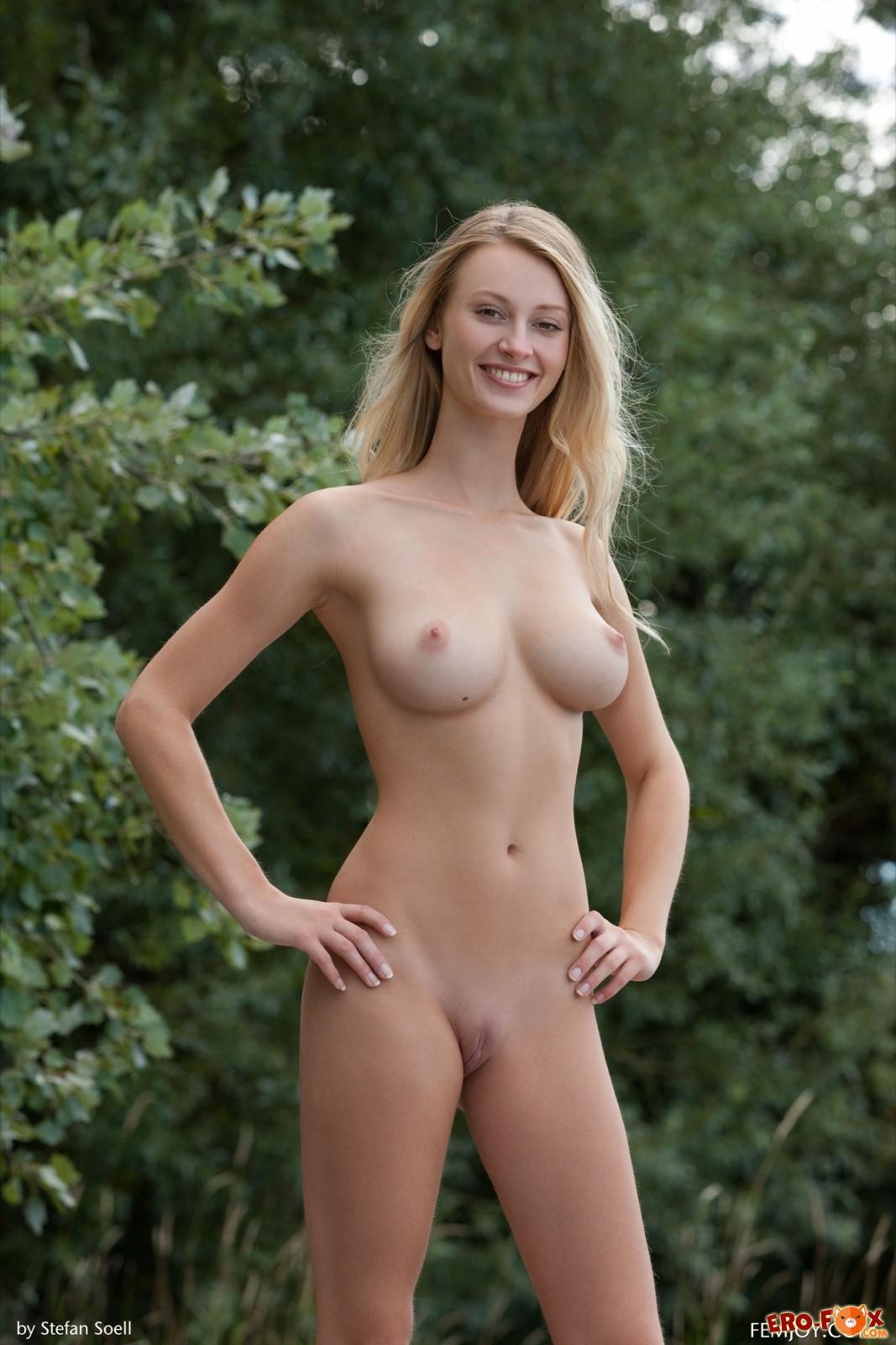 Голая блондинка с упругой грудью гуляет на природе
