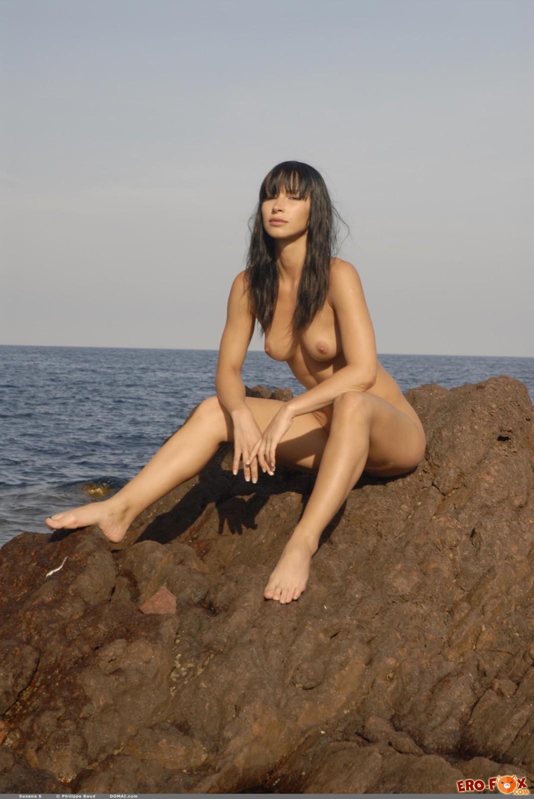 Привлекательная голая девушка позирует рядом с морем