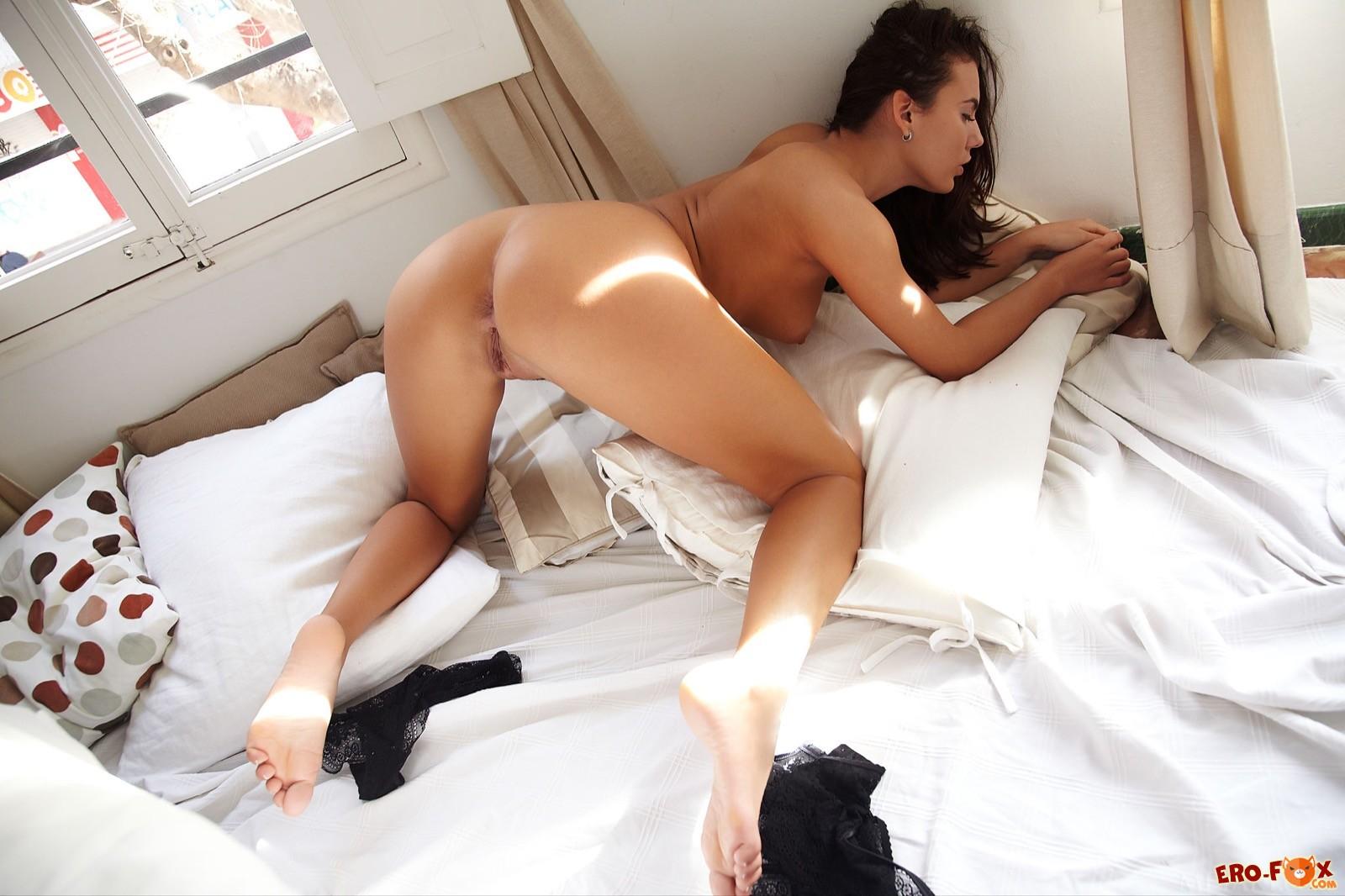 Загорелая красавица раздвигает ноги лежа на кровати