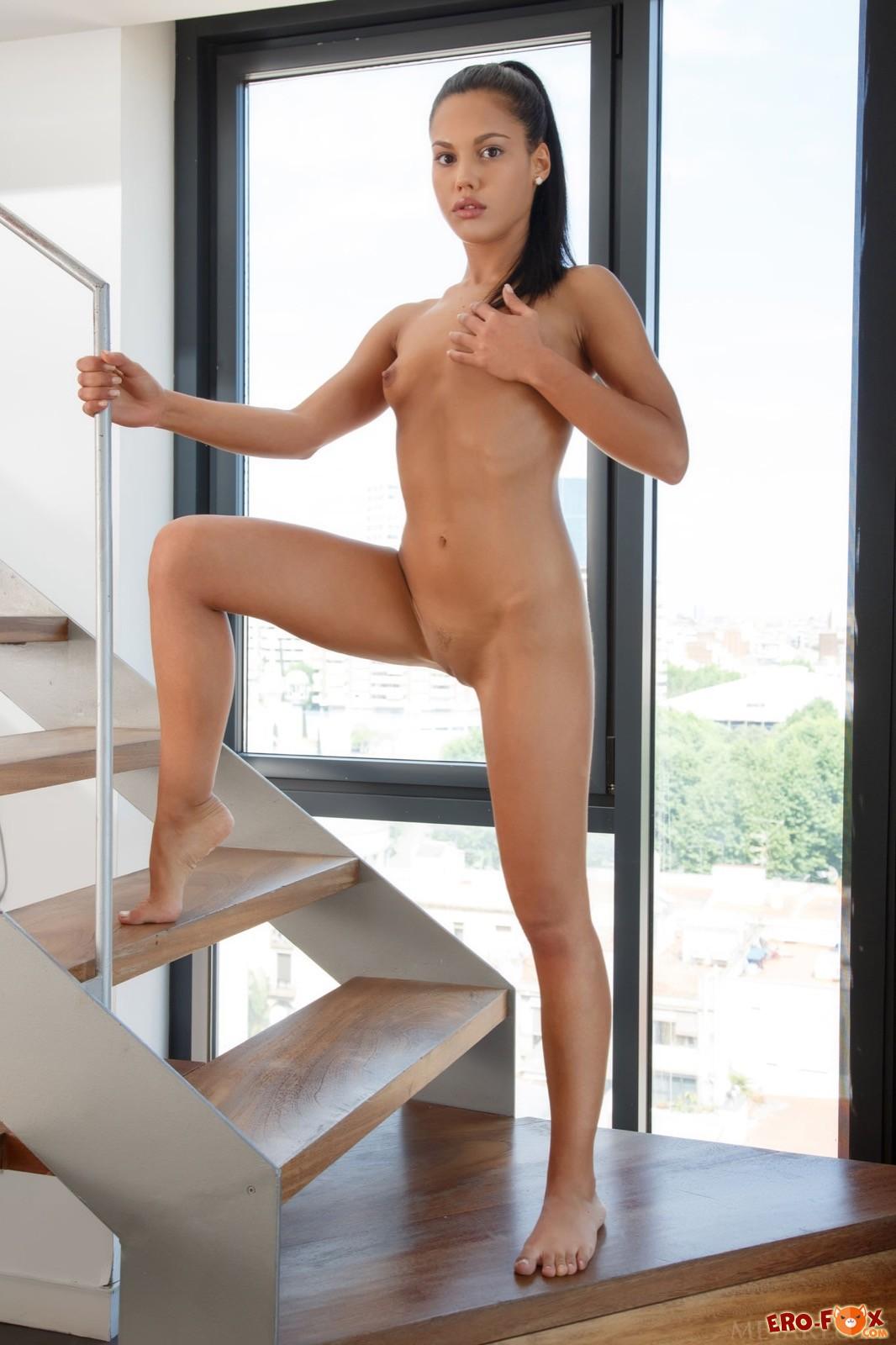 Маленькая грудь голой девушки позирующей на лестнице
