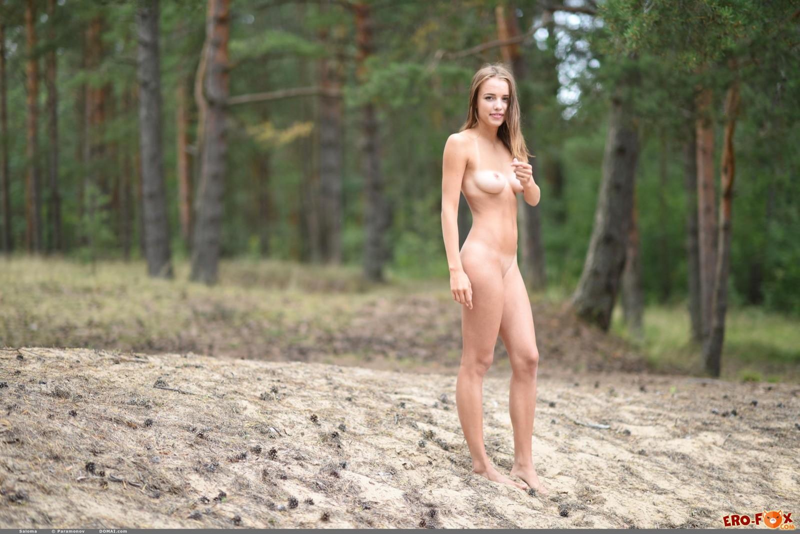 Худенькая девушка с подтянутой грудью гуляет по лесу