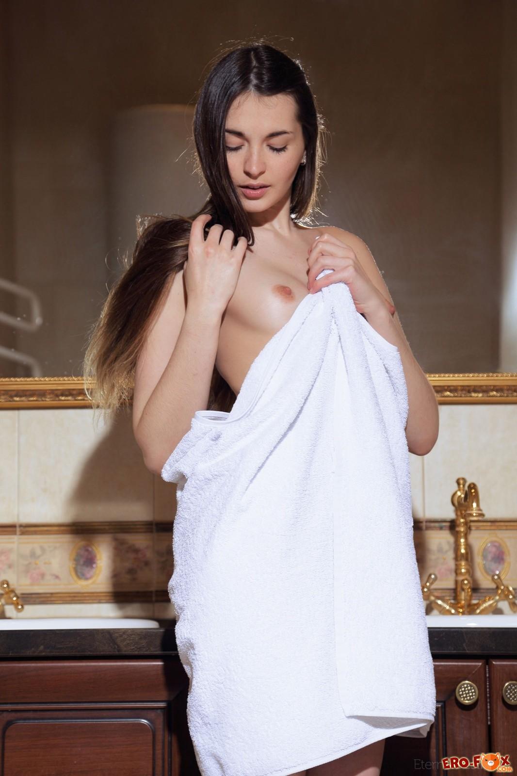 Голая милашка обливает бритую письку водой в ванной