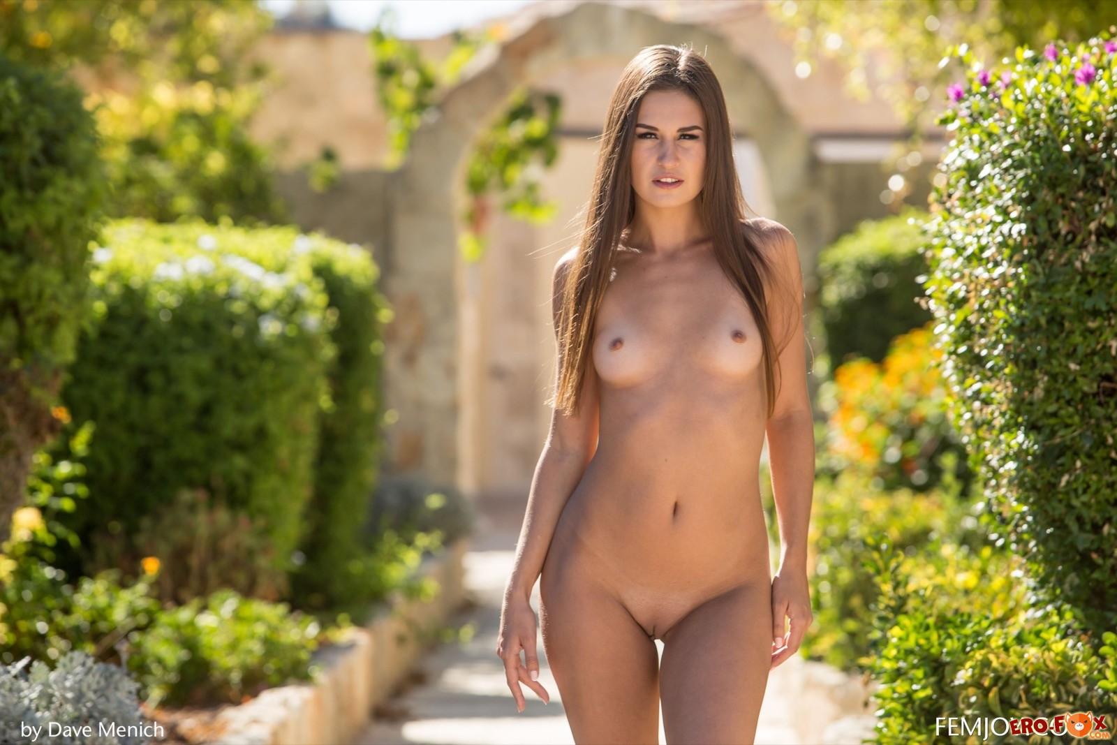 Сексуальная красотка сняв платье позирует на улице