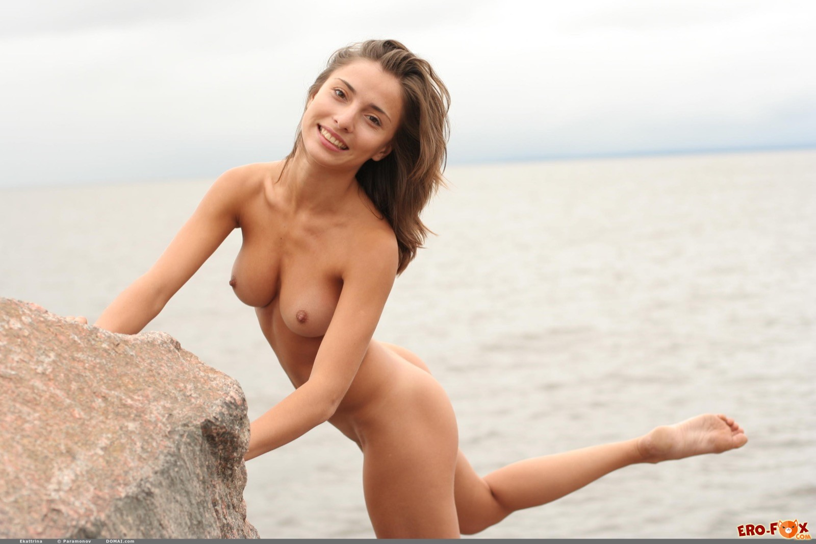 Голая шатенка с красивым телом позирует у моря