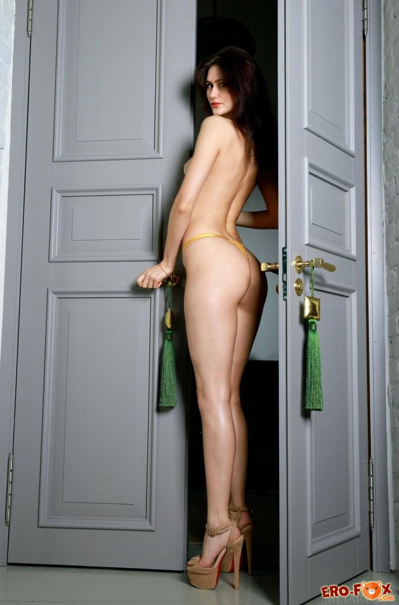 Голая девушка с красивой жопой стоит в дверях.