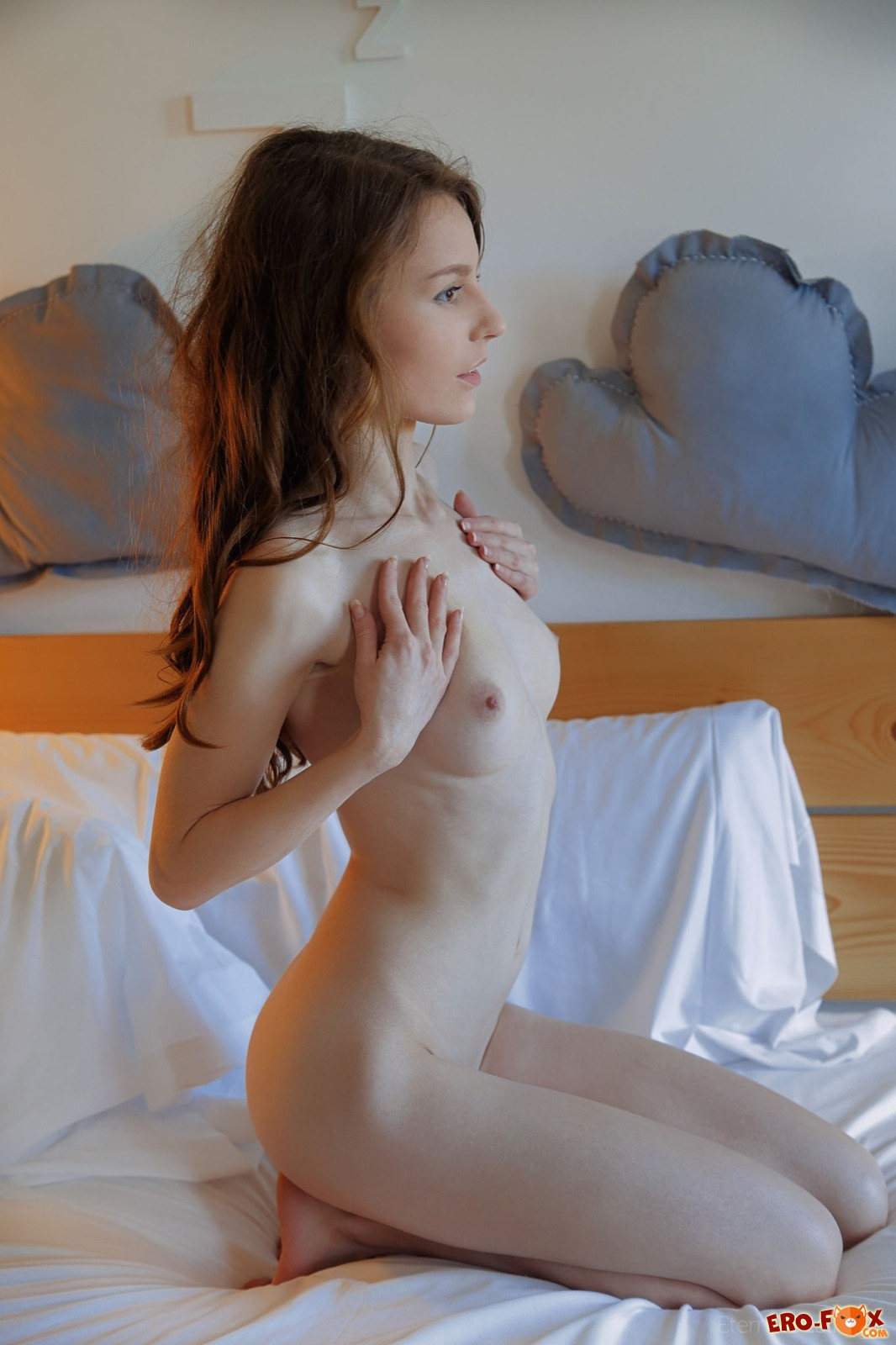 Голая брюнетка на кровати  эротика