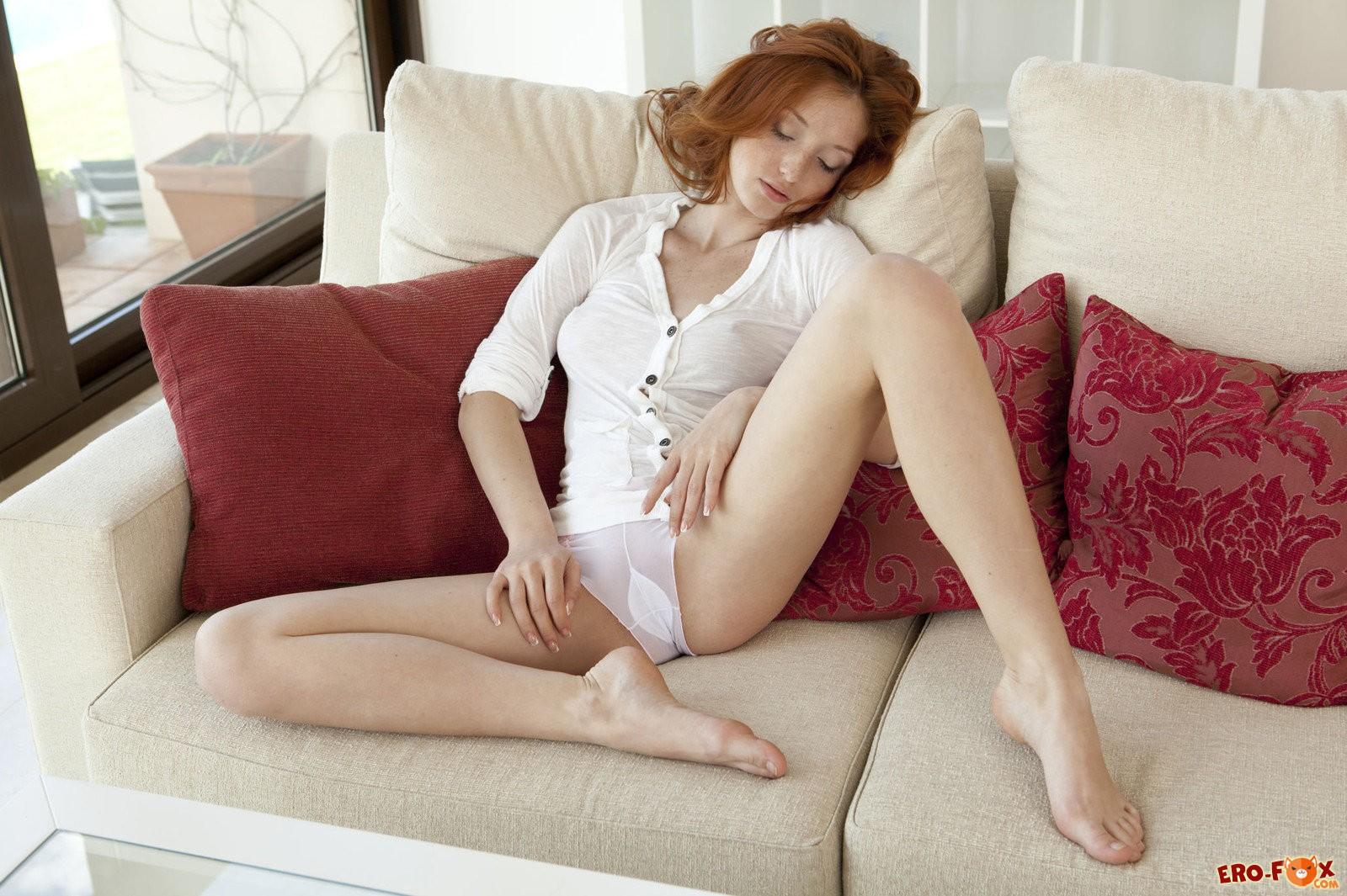 Рыжая бесстыжая девушка голая на диване .