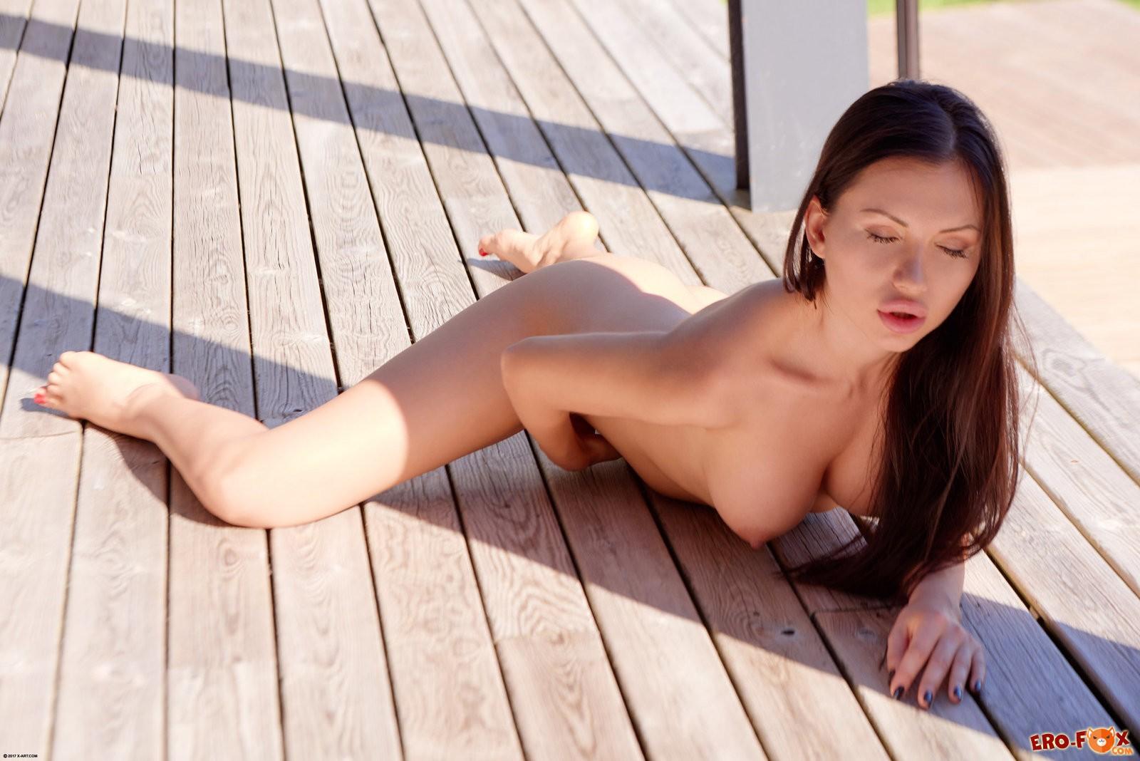 Сексуальная брюнетка загорает голая .