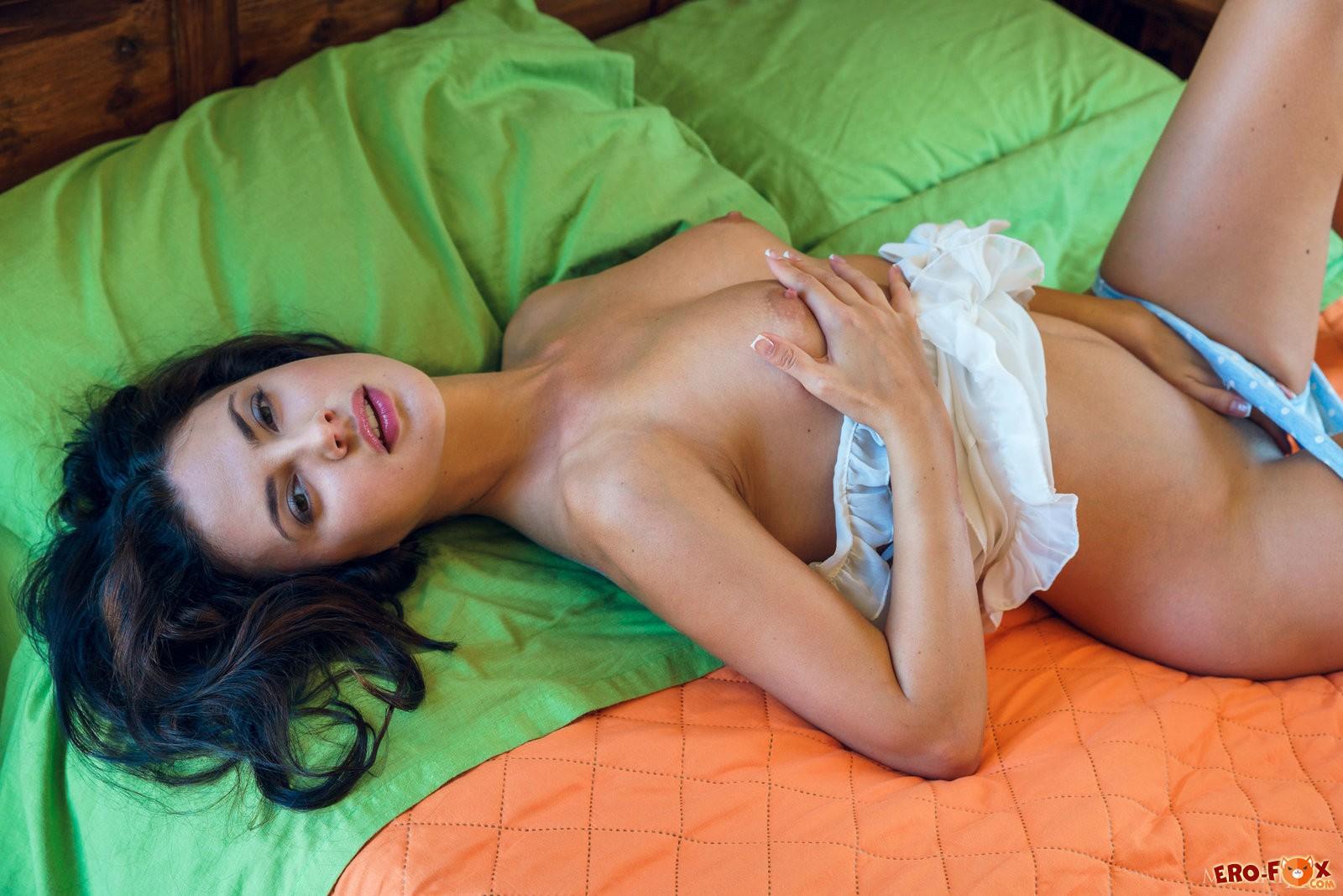 Девушка снимает трусики в постели .