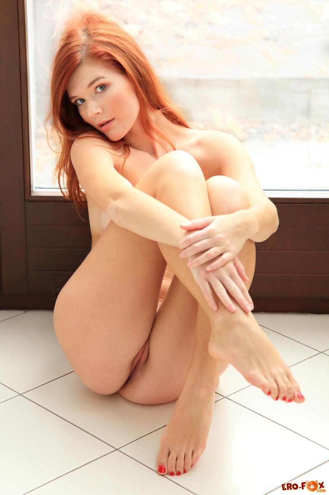 Голая рыжая девушка с упругой грудью .