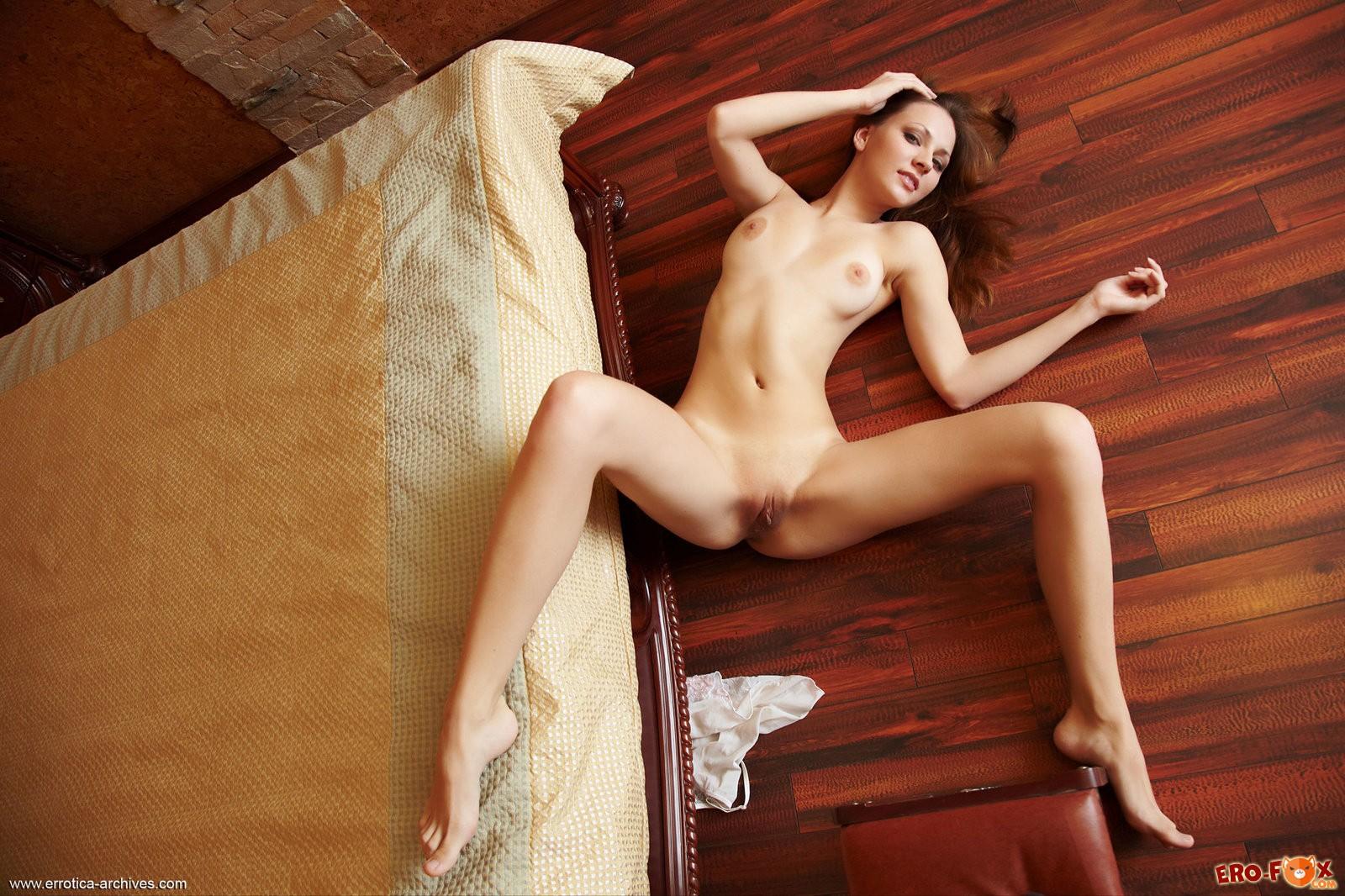 Голая девушка лежит на полу  в спальне.