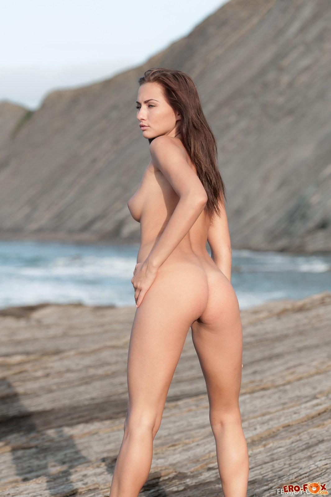 Голая девушка с красивой упругой грудью на побережье .